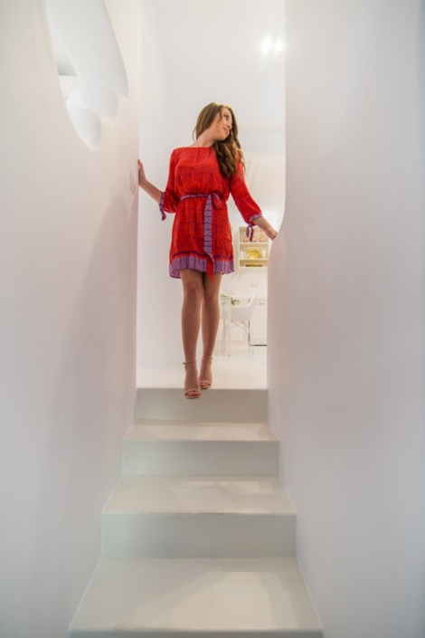 Woman in a red dress walking down the stairs of Villa Luana